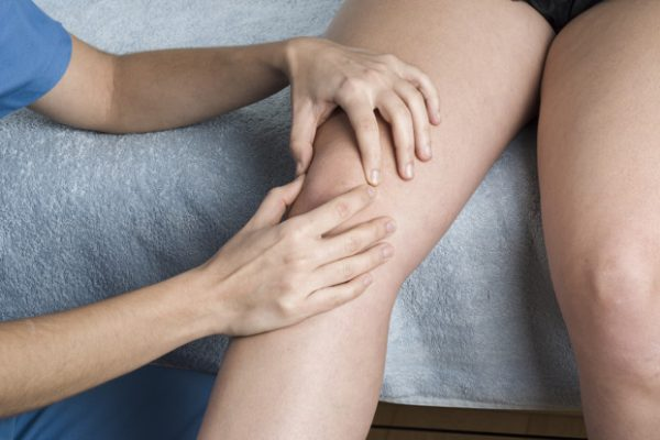 Physiotherapist, chiropractor doing a patellar mobilization, Knee pain.